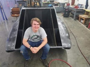 Industrial design major and Raleigh native John Lalevee poses with the unfinished solar vehicle, which he helped design during the 2017–18 year. Photo submitted